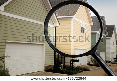 Magnifying glass looking at suburban houses - stock photo