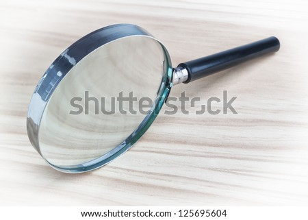 Magnifying glass magnifying glass on a wooden texture. - stock photo