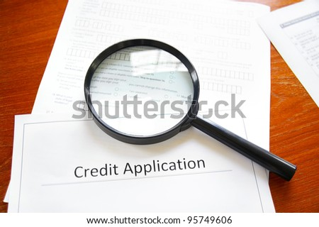 magnifying glass on a blank credit application - stock photo