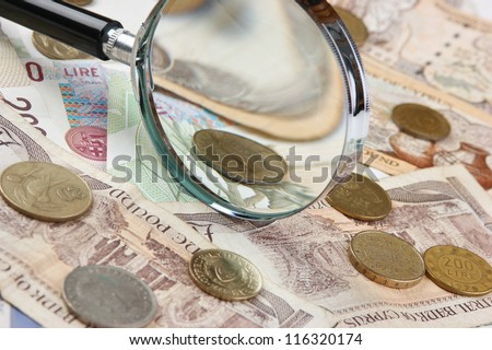 magnifying glass on a pile of old European money