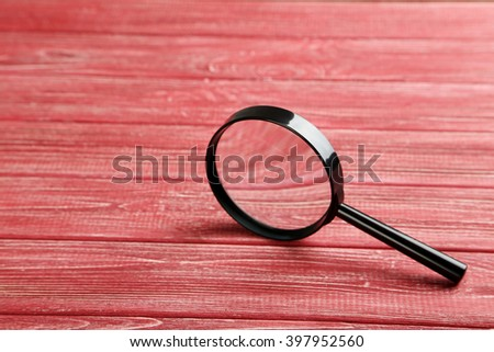 Magnifying glass on a red wooden table - stock photo