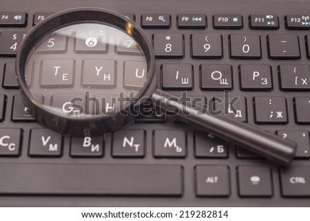 Magnifying Glass on black keyboard - stock photo