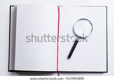 Magnifying glass on blank book open with white pages with copyspace - stock photo