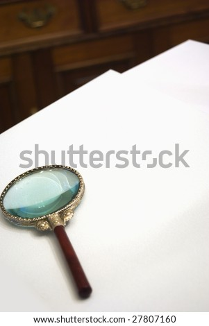 Magnifying glass on blank paper with desk in background.  Customization space for text or document insert. - stock photo