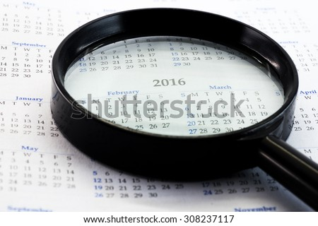Magnifying glass on calendar emphasis on 2016