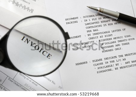 Magnifying glass on invoice text with pen on purchase and sales related documents in background. For business and office life, and sales and purchase concepts. - stock photo