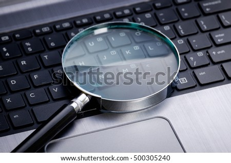 Magnifying glass on laptop keyboard; online search, online shopping, business concepts.