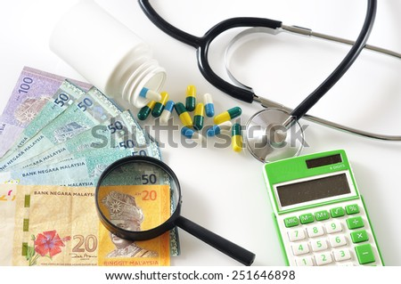 Magnifying Glass On Malaysian Bank Note with Spill Out of Capsule Pill, Stethoscope and Calculator,  Medical Care Cost Concept and Selective Focus   - stock photo