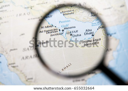 Magnifying glass on map with focus on Qatar