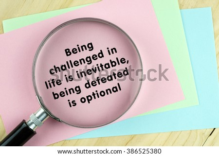 """Magnifying glass on papers with word quote of """"Being challenged in life is inevitable,being defeated is optional"""" written on it. - stock photo"""