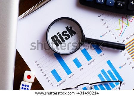"Magnifying glass on ""Risk"" text on chart, dice, spectacles, pen, laptop calculator on wooden table - business, banking, finance and investment concept"