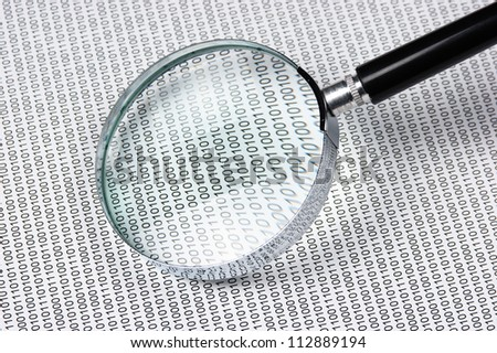 magnifying glass on the background of a binary code - stock photo
