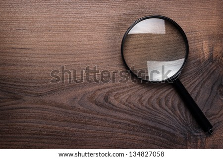 magnifying glass on the brown wooden background - stock photo