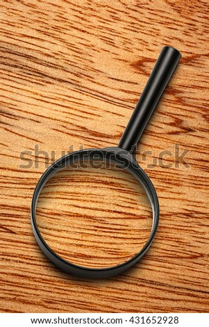 Magnifying glass on the wooden background closeup - stock photo