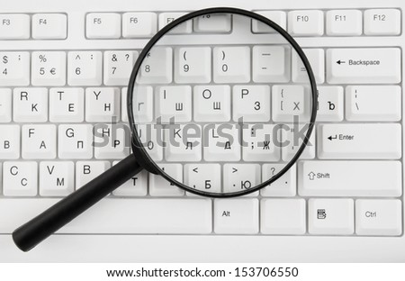 Magnifying glass on white keyboard close up