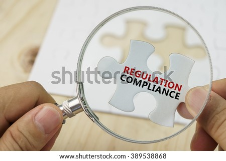 Magnifying glass on white puzzle with word REGULATION and COMPLIANCE. - stock photo