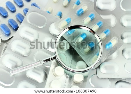Magnifying glass on wraps of pills. - stock photo