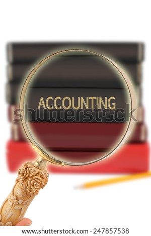 Magnifying glass or loop looking on an educational subject - Accounting - stock photo