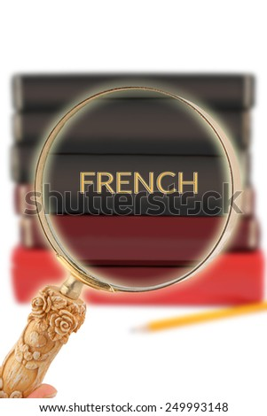 Magnifying glass or loop looking on an educational subject - French - stock photo