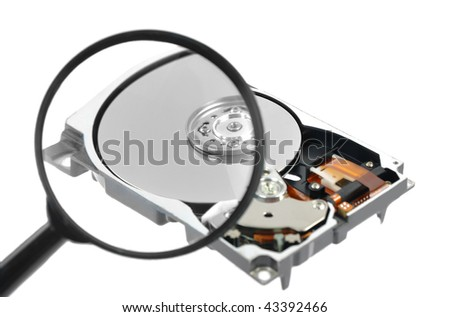 Magnifying glass over a computer harddrive - stock photo