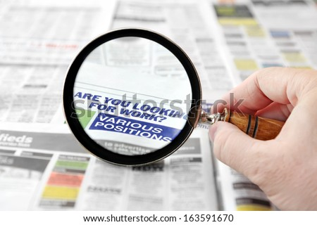 Magnifying glass over a newspaper job search section  - stock photo