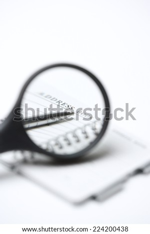 Magnifying glass over address book and pen, close-up - stock photo