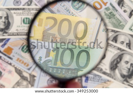 Magnifying glass over euro notes. US dollar in the background