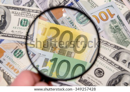 Magnifying glass over euro notes. US dollar in the background - stock photo
