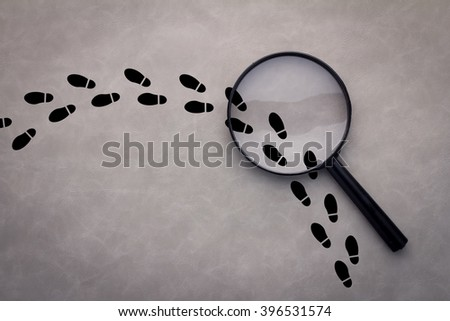 Magnifying glass over footsteps on grey background - stock photo