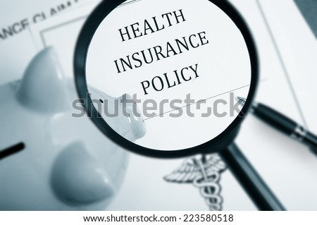 Magnifying glass over health insurance policy and piggy bank - stock photo