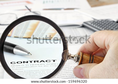 "Magnifying Glass Over  Papers and Word ""Contract""in Focus - stock photo"