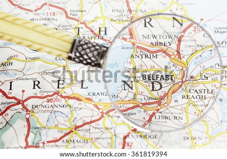 Magnifying glass over the map, focusing on Belfast. - stock photo