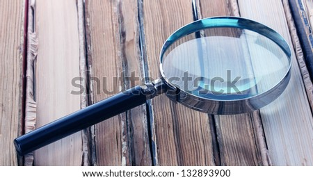 Magnifying glass over the stack of books