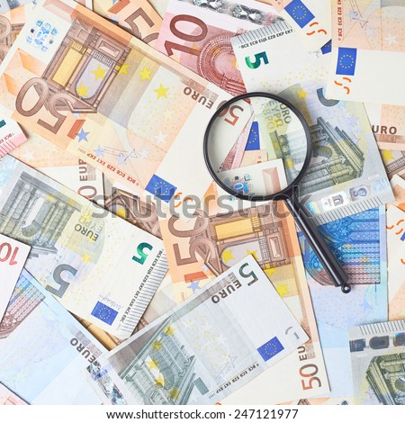 Magnifying glass over the surface covered with multiple euro bank note bills