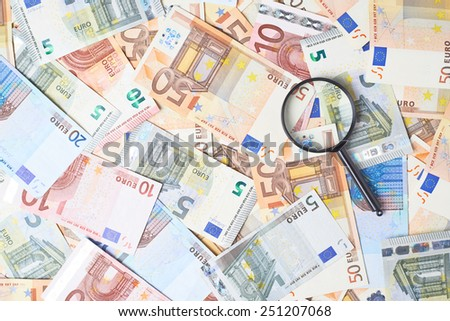 Magnifying glass over the surface covered with multiple euro bank note bills - stock photo