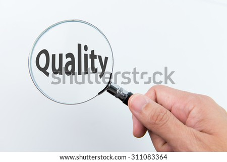 Magnifying glass over the word quality on white background