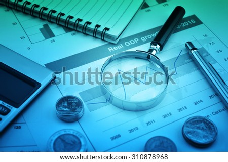 Magnifying glass, pen and calculator on financial chart and graph, accounting background - stock photo