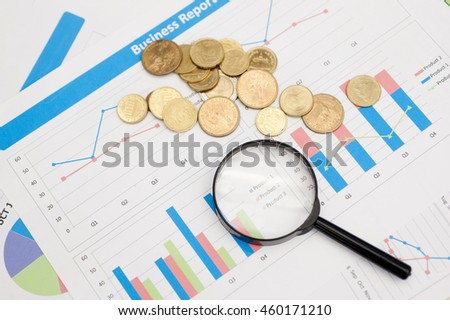Magnifying glass placed on a sheet of graph paper, statistics and market research.