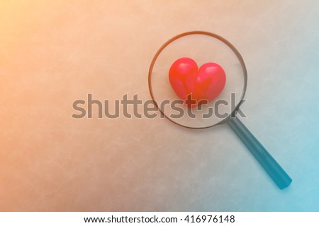Magnifying glass & red heart  on color background - stock photo