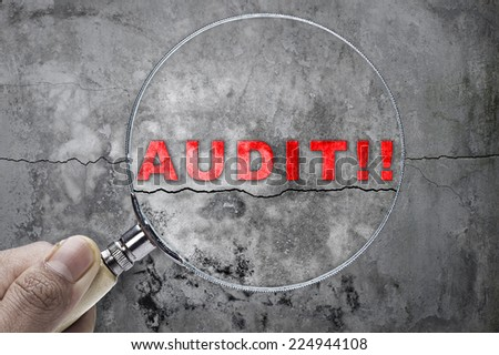 "Magnifying glass searching ""audit"" over cracked wall as a background - stock photo"