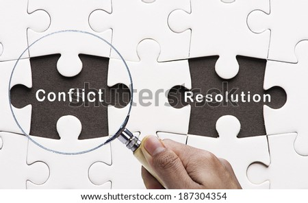 "Magnifying glass searching missing puzzle peace ""Conflict Resolution"" - stock photo"