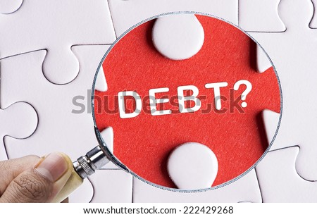 "Magnifying glass searching missing puzzle peace ""DEBT"" - stock photo"