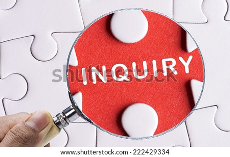 """Magnifying glass searching missing puzzle peace """"INQUIRY"""" - stock photo"""