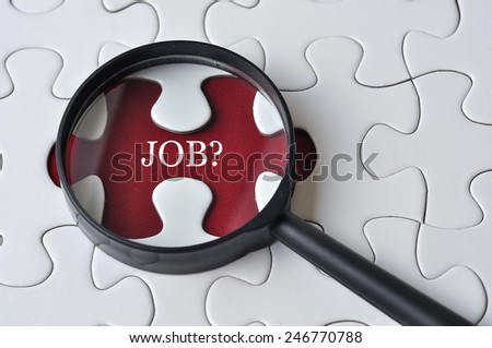 """Magnifying glass searching missing puzzle peace """"JOB"""" - stock photo"""