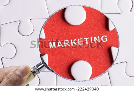 """Magnifying glass searching missing puzzle peace """"MARKETING"""" - stock photo"""