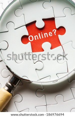 """Magnifying glass searching missing puzzle peace """"ONLINE"""" - stock photo"""