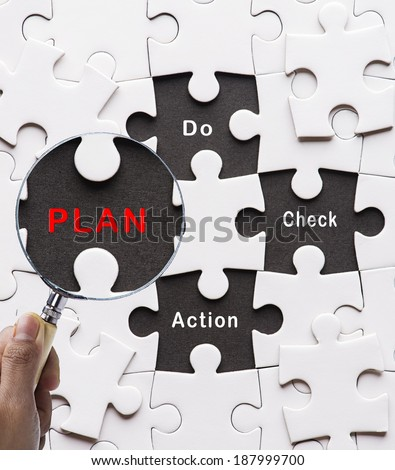 """Magnifying glass searching missing puzzle peace """"Plan"""" - stock photo"""