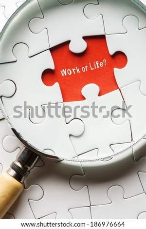"Magnifying glass searching missing puzzle peace ""WORK OR LIFE"" - stock photo"