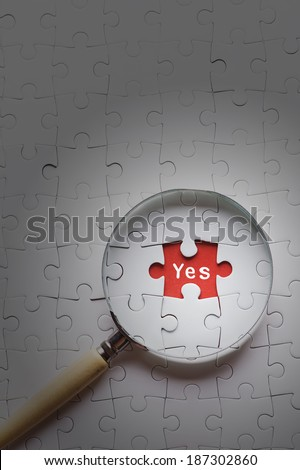 "Magnifying glass searching missing puzzle peace ""YES""; - stock photo"