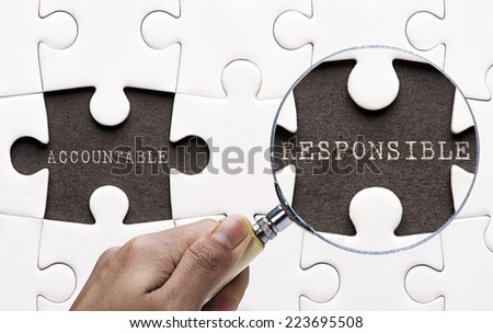 "Magnifying glass searching missing puzzle peaces ""Responsible and accountable"" - stock photo"